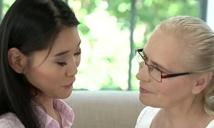 Asian teen tutoring an grey woman